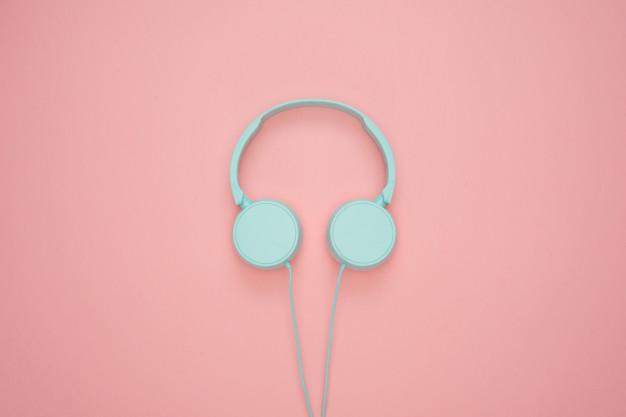 Fondo de audifonos celestes pastel en fondo rosa pastel